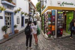 Dos chicas jóvenes toman la foto en la calle de Romero, cuarto judío Imágenes de archivo libres de regalías