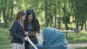 Dos chicas jóvenes utilizan la tableta y hablar en el parque almacen de video