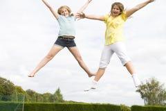Dos chicas jóvenes que saltan en la sonrisa del trampolín Fotografía de archivo