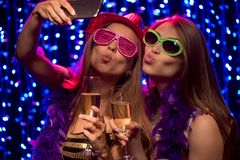 Dos chicas marchosas con los vidrios de shampagne Foto de archivo libre de regalías