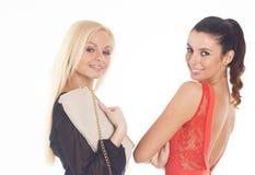 Dos chicas marchosas hermosas en fondo aislado blanco Imagen de archivo libre de regalías