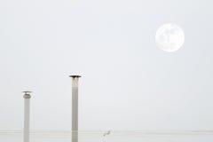 Dos chimeneas y la luna mientras que una gaviota está volando cruzando un cielo gris Fotografía de archivo libre de regalías