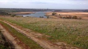 Dos ciclistas en el horizonte Tiempo ventoso en el río Carretera nacional almacen de video
