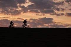 Dos ciclistas en la puesta del sol Imágenes de archivo libres de regalías