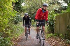 Dos ciclistas masculinos maduros que montan las bicis a lo largo de la trayectoria Foto de archivo libre de regalías
