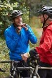 Dos ciclistas masculinos maduros que montan las bicis a lo largo de la trayectoria Imagenes de archivo