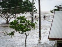 Dos ciclistas por el mar durante las inundaciones de Brisbane Imágenes de archivo libres de regalías
