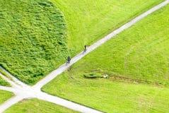 Dos ciclistas se acercan a una juntura en un campo verde Fotos de archivo libres de regalías