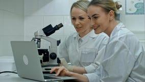 Dos científicos positivos jovenes que trabajan en laboratorio usando el microscopio y el ordenador portátil Imagen de archivo libre de regalías