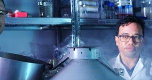 Dos científicos que cubren la tapa del barril 4k almacen de video