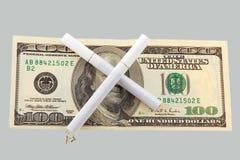 Dos cigarrillos cruzados sobre cientos dólares Fotos de archivo libres de regalías