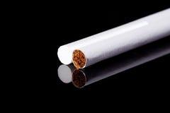 Dos cigarrillos finos aislados en macro negra del fondo Fotografía de archivo