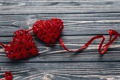 Dos cintas rojas elegantes de los corazones en fondo de madera rústico negro Imágenes de archivo libres de regalías