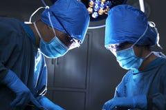 Dos cirujanos que miran abajo, trabajando, y concentrando en la mesa de operaciones Fotos de archivo libres de regalías