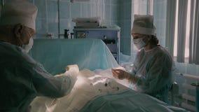 Dos cirujanos que realizan una operación y una enfermera que ayuda a la cirugía almacen de video