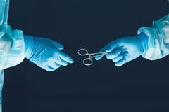 Dos cirujanos que trabajan y que pasan el equipo quirúrgico en la sala de operaciones Imagen de archivo libre de regalías