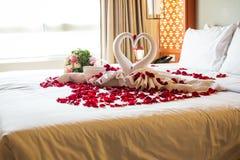 Dos cisnes hechos de las toallas se están besando en cama del blanco de la luna de miel Imagen de archivo libre de regalías