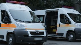 Dos coches de la ambulancia cerca del hospital, lugar del tratamiento del transporte, asistencia médica almacen de video