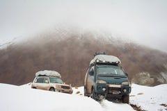 Dos coches de viajeros en el camino de la nieve de la montaña ajardinan coche en un paso de montaña, pico del jeep 4x4 del soport fotografía de archivo libre de regalías