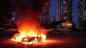 Dos coches queman en estacionamiento con el highrise en la oscuridad almacen de metraje de vídeo
