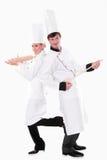 Dos cocineros con los utensilios de la cocina fotos de archivo libres de regalías