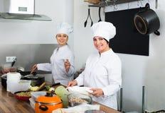 Dos cocineros de las mujeres jovenes que cocinan la comida en la cocina Foto de archivo
