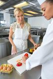 Dos cocineros de sexo femenino que trabajan al lado de uno a en cocina del hotel imagen de archivo