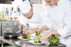 Dos cocineros preparan el plato del filete en el restaurante gastrónomo imágenes de archivo libres de regalías
