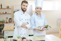 Dos cocineros que presentan en cocina imagen de archivo libre de regalías