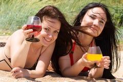 Dos cocteles de la bebida de las chicas jóvenes en la playa Fotos de archivo