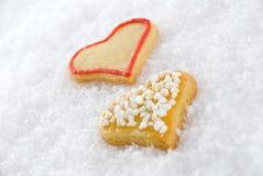 Dos cokkies del corazón en la nieve Fotografía de archivo libre de regalías