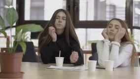 Dos colegas cansados son bostezo dormido mientras que se sientan en una tabla en una oficina de negocios moderna Concepto de nego metrajes