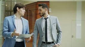 Dos colegas de los hombres de negocios que caminan y que discuten documentos en pasillo moderno de la oficina