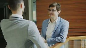 Dos colegas del hombre de negocios que colocan y que charlan la verja cercana derecha en pasillo del centro de negocios moderno almacen de metraje de vídeo