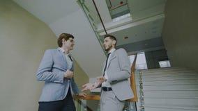 Dos colegas del hombre de negocios que colocan y que charlan la verja cercana derecha en pasillo del centro de negocios moderno
