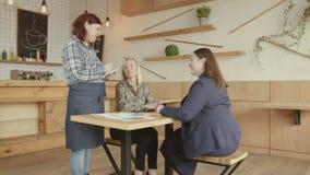 Dos colegas del negocio de las mujeres que hacen orden en café almacen de metraje de vídeo