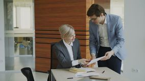 Dos colegas del negocio que discuten informes en oficina moderna Empresaria que se sienta en la tabla que habla a su socio mascul