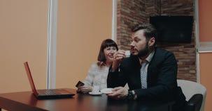Dos colegas en el café que se sienta en la mesa de centro y que usa la compra de la tarjeta y del ordenador portátil algo almacen de metraje de vídeo