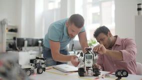 Dos colegas masculinos que construyen la máquina robótica