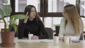 Dos colegas que charlan y que beben el café mientras que se sienta en una tabla en una oficina de negocios moderna durante una ro almacen de metraje de vídeo