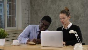 Dos colegas que discuten datos sobre el ordenador portátil que pone notas en el suelo metrajes