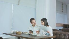Dos colegas que discuten el trabajo mientras que come el almuerzo en un café almacen de metraje de vídeo
