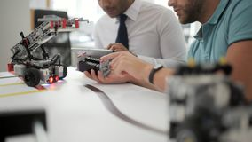 Dos colegas que examinan las máquinas robóticas en estudio