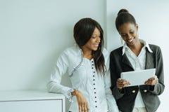 Dos colegas que hablan del contenido en una PC de la tableta en nosotros fotos de archivo libres de regalías