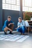 Dos colegas que hablan junto sobre papeleo en un piso de la oficina Fotos de archivo