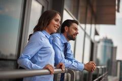 Dos colegas que se colocan en balcón para tener rotura foto de archivo libre de regalías