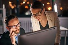 Dos colegas que trabajan en el ordenador en la noche fotos de archivo
