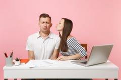 Dos colegas sonrientes del hombre de la mujer de negocios sientan el trabajo en el escritorio blanco con el ordenador portátil co fotografía de archivo libre de regalías