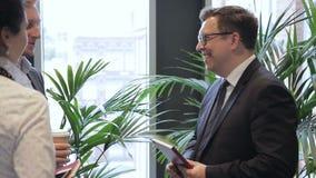 Dos colegas tienen una conversación informal con el jefe en el pasillo brillante de la oficina metrajes