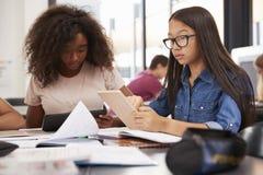 Dos colegialas adolescentes que usan las tabletas en clase Imagenes de archivo